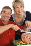 Beautiful couple slicing ham Stock Photography