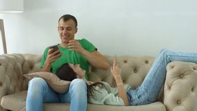 Happy couple with smart phones relaxing at home stock video footage