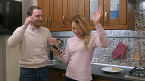 Beautiful couple is smiling while dancing and listening music via smartphone in kitchen at home stock video