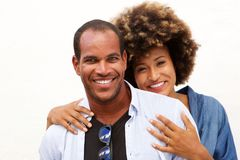 Beautiful couple smiling in embrace by white wall. Close up portrait of beautiful couple smiling in embrace by white wall Stock Images