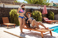 Beautiful couple smiling, speaking, drinking cocktails, sitting near swimming pool. Royalty Free Stock Photo