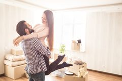 Beautiful couple are standing in a bright room with unpacked boxes. Young man is holding his attractive wife in hands. Beautiful couple are standing in a bright stock image