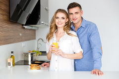 Beautiful Couple Standing On Kitchen With Pancakes And Fresh  Juice