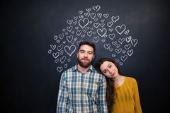 Beautiful couple standing over black board with drawn hearts Stock Photography