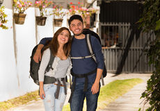 Beautiful couple standing together wearing casual clothing and backpacks, posing for camera smiling positive attitude Royalty Free Stock Images
