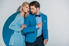 Beautiful couple in stylish blue suit and dress standing together in aperture. On grey stock photography