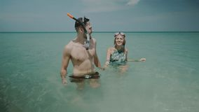Beautiful couple during summer holidays. Young happy couple with snorkeling masks having fun in the sea water, enjoying sunny summer day on their beach tropical Stock Images