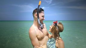 Beautiful couple during summer holidays. Young happy couple with snorkeling masks having fun in the sea water, enjoying sunny summer day on their beach tropical Royalty Free Stock Photos