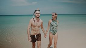 Beautiful couple during summer holidays. Young happy couple with snorkeling masks walking out from sea water, enjoying sunny summer day on their beach tropical Stock Photo