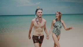 Beautiful couple during summer holidays. Young happy couple with snorkeling masks walking out from sea water, enjoying sunny summer day on their beach tropical Stock Image