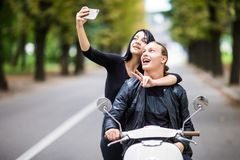 Beautiful couple in sun glasses is doing selfie using a smart phone and smiling while sitting on a scooter outdoors Royalty Free Stock Image