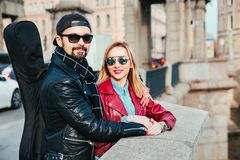 Beautiful couple in sunglasses on the bridge in city . Rock style . Couple in love Stock Photography