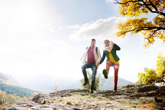 Beautiful couple in sunny autumn nature, jumping on a rock Stock Images