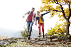 Beautiful couple in sunny autumn nature, running on a rock Royalty Free Stock Images