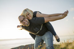 Beautiful couple at the sunset habing fun on seaside Stock Photo