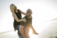 Beautiful couple at the sunset habing fun on seaside Stock Photography