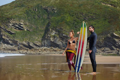 Beautiful couple surfers  standing on the beach a girl   in a bathing  a guy  holding surfboard Royalty Free Stock Photos