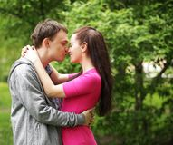 Beautiful couple in a sweet cheek kiss Stock Images