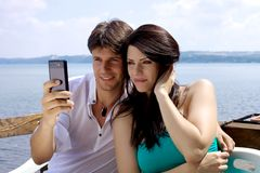 Beautiful couple taking picture in front of lake Stock Image