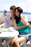 Beautiful couple taking pictures of themselves in vacation in front of lake Royalty Free Stock Image