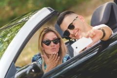 Beautiful couple taking self portrait from their cabriolet car in nature. stock images