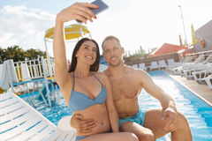 Beautiful couple taking selfie near swimming pool Royalty Free Stock Images