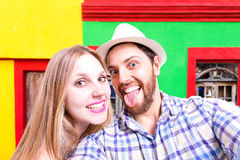 Beautiful Couple taking a selfie photo in a colorful background Beautiful Couple taking a selfie photo in a colorful background Royalty Free Stock Images