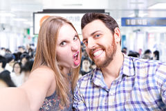Beautiful Couple taking a selfie photo in Tokyo Subway, Japan.  Royalty Free Stock Images