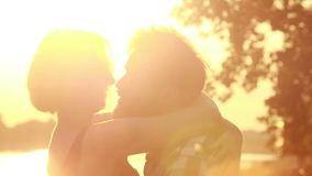 Beautiful couple talking and laughing while sitting by the river at sunset. Close up of beautiful happy couple looking at each other, laughing and talking while stock video