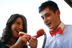 Beautiful couple talking into a red telephone Royalty Free Stock Image