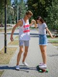 An attractive smiling fellow teaching a girl riding on a longboard in a park on a natural blurred background. Royalty Free Stock Photos