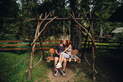 Beautiful couple together with dog on a swing Royalty Free Stock Photo