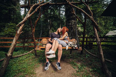 Beautiful couple together with dog on a swing Royalty Free Stock Photos