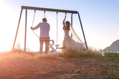 Beautiful couple together on swings at sunset. Stock Image