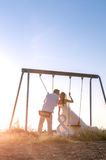 Beautiful couple together on swings at sunset. Royalty Free Stock Photo