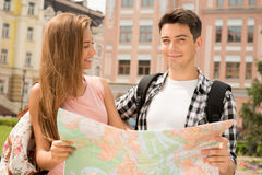 Beautiful couple of tourists holding a map in. Close-up portrait of a beautiful couple of tourists holding a map in their hands boy happy looking at the camera Royalty Free Stock Image