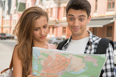 Beautiful couple of tourists holding a map in. Close-up portrait of a beautiful couple of tourists holding a map in their hands, a girl looking very astonished Stock Photography