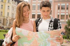 Beautiful couple of tourists holding a map in. Close-up portrait of a beautiful couple of tourists holding a map in their hands girl pretty smiling boy Stock Photography