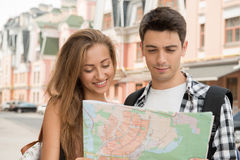 Beautiful couple of tourists holding a map in. Close-up portrait of a beautiful couple of tourists holding a map in their hands, a girl pretty smiling and a boy Royalty Free Stock Photography
