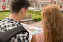Beautiful couple of tourists holding a map in Stock Image