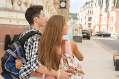 Beautiful couple of tourists holding a map in. Waist-up portrait of a beautiful couple of tourists standing back to the camera holding a map in their hands and Royalty Free Stock Image