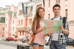 Beautiful couple of tourists holding a map in. Waist-up portrait of a beautiful couple of tourists holding a map in their hands and both looking at the camera Stock Photos
