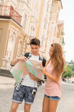 Beautiful couple of tourists holding a map in. Waist-up portrait of a beautiful couple of tourists holding a map in their hands and both looking at the map and Stock Photography