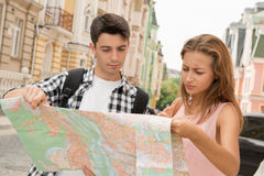 Beautiful couple of tourists holding a map in Royalty Free Stock Photo