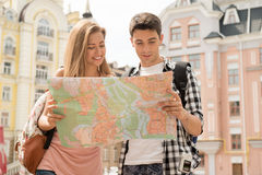 Beautiful couple of tourists holding a map in. Waist-up portrait of a beautiful couple of tourists holding a map in their hands and both looking at the map and Royalty Free Stock Images