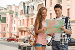 Beautiful couple of tourists holding a map in. Waist-up portrait of a beautiful couple of tourists holding a map in their hands and both looking at the map and Royalty Free Stock Photo