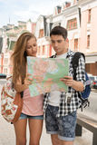 Beautiful couple of tourists holding a map in. Waist-up portrait of beautiful couple of tourists holding a map in their hands, a girl looking astonished and Stock Photos
