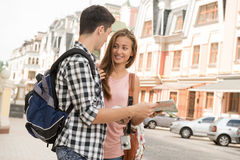 Beautiful couple of tourists holding a map in. Waist-up portrait of a beautiful couple of tourists holding a map in their hands and smiling looking on each other Stock Photos