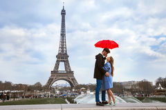 Beautiful couple with umbrella near Eiffel Tower. Honeymoon in Paris, romantic moment royalty free stock images