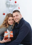 Beautiful couple under Christmas tree with gift in hands royalty free stock image